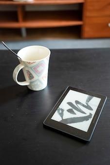 Eine tasse mit löffel innen und e-book auf schwarzem tisch