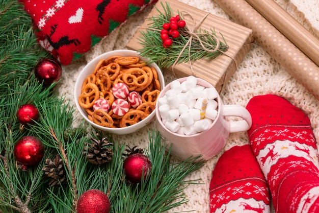 Eine tasse mit marshmallow-geschenkbox craft wrapper zweig eines weihnachtsbaums eine schüssel brezeln