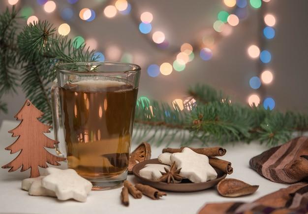 Eine tasse mit tee, lebkuchen und christbaumzweigen