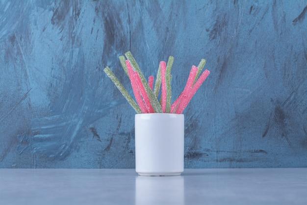 Eine tasse mit zuckerhaltigen gelee-fruchtstangen bonbons auf grauem hintergrund. foto in hoher qualität