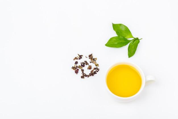 Eine tasse oolong-tee mit frischen blättern und einem haufen trockenen grünen tees auf weißem hintergrund, mit kopierraum für text. bio-kräutertee, grüner asiatischer tee für die teezeremonie. flach liegen