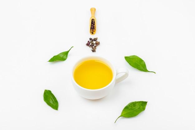 Eine tasse oolong-tee mit frischen blättern und einem haufen trockenen grünen tees auf weißem hintergrund, mit kopierraum für text