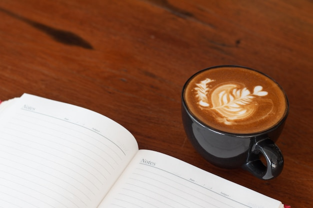 Eine tasse piccolo latte-kunst auf hölzernem schreibtisch, entspannende zeit oder kaffeepause während des arbeitstages