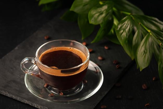 Eine tasse schwarzen duftenden frisch gebrühten kaffee auf dem tisch
