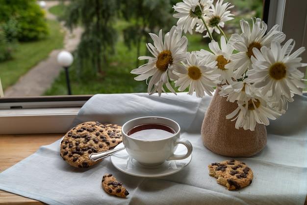 Eine tasse schwarzen kaffee auf der fensterbank unter den sonnenstrahlen, neben schönen blumen, vertikaler schuss.