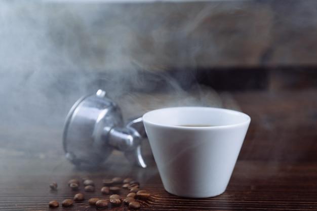 Eine tasse schwarzen kaffee, geröstete kaffeebohnen und ein espressomaschinenhalter auf einem dunklen hintergrund.