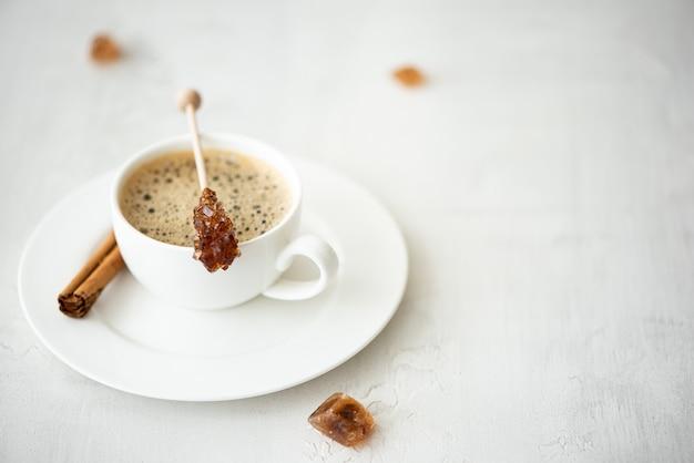Eine tasse schwarzen kaffee mit zimt und karamellisiertem zucker am stiel auf einem weißen tisch