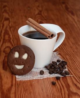 Eine tasse schwarzen kaffee mit zimtstange neben gerösteten kaffeebohnen und keksen.