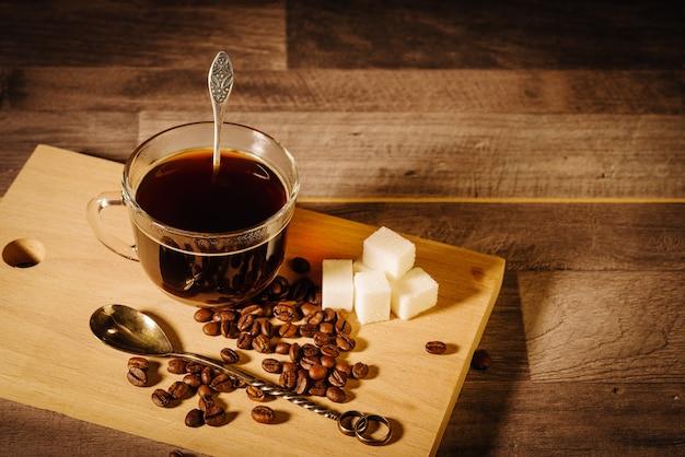Eine tasse schwarzen kaffee mit zuckerstückchen und kaffeebohnen auf dem tisch