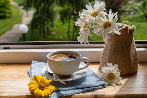 Eine tasse schwarzen kaffee und gartenblumen auf der fensterbank unter den sonnenstrahlen und schöne blumen.