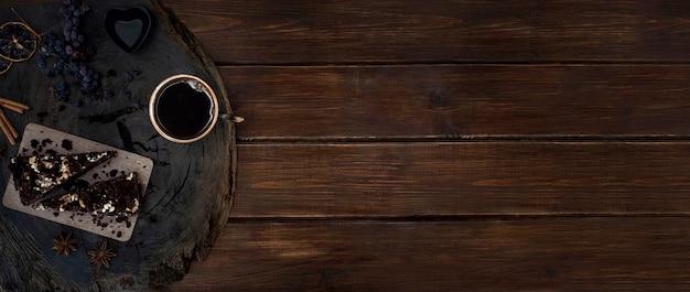 Eine tasse schwarzen kaffees mit stücken schokoladenkuchen auf einem geschnittenen hölzernen eichenholzschnitt. banner mit kopierplatz