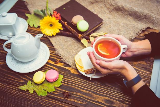 Eine tasse schwarzen tee mit zitrone wärmt die palmen