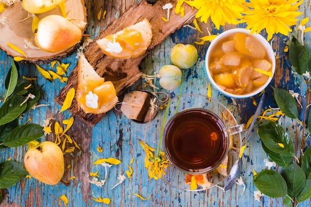 Eine tasse schwarzen tee und marmelade aus birnen in einer schüssel und auf einem stück brot, ansicht von oben