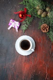 Eine tasse schwarztee-tannenzweige dekorationszubehör und geschenk auf dunklem hintergrund