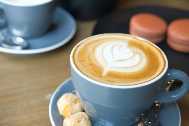 Eine tasse späten kaffees mit blumenformentwurf oben am café