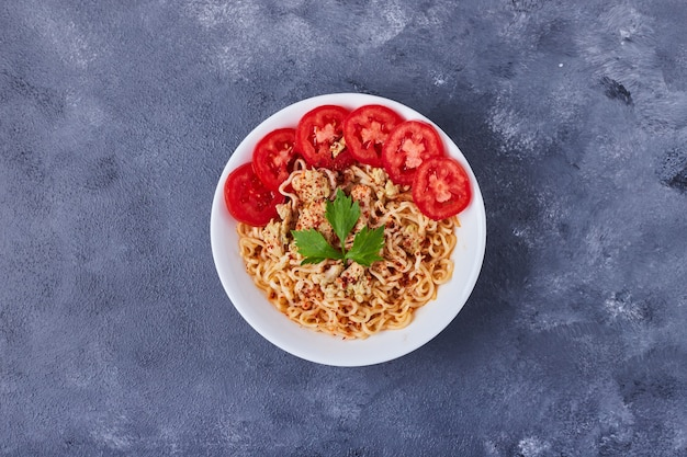 Eine tasse spaghetti mit tomatenscheiben.