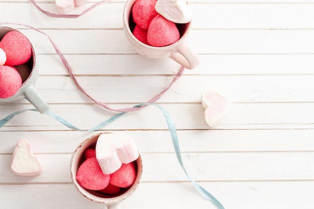 Eine tasse süße und herzförmige marshmallows zum valentinstag, geburtstagsfeier, babyparty. speicherplatzhintergrund kopieren. draufsicht.