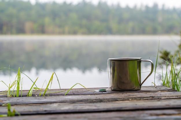 Eine tasse tee am waldsee. camping-, trekking- und wanderkonzept. outdoor-aktivitäten stockfoto.