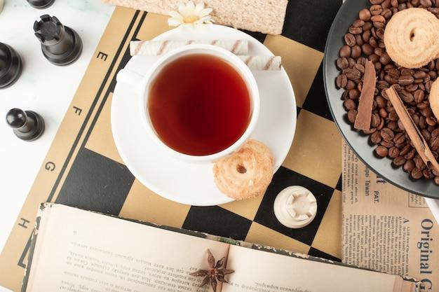 Eine tasse tee auf dem käsebrett mit figuren herum