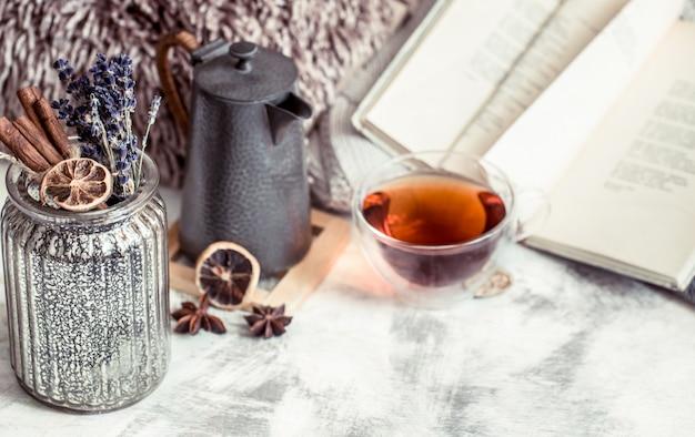 Eine tasse tee auf dem tisch mit buch und gewürzen