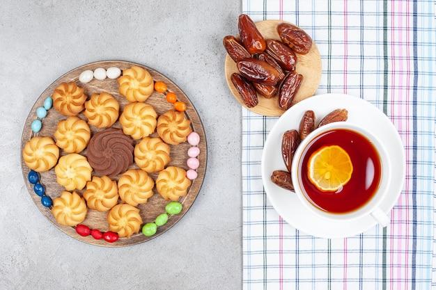 Eine tasse tee auf einem handtuch mit datteln und einem holztablett mit arrangierten keksen und süßigkeiten auf marmorhintergrund. hochwertiges foto