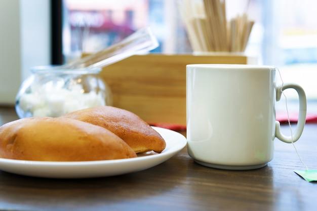 Eine tasse tee auf einem holztisch mit einem brötchen am fenster. das konzept eines morgenfrühstücks
