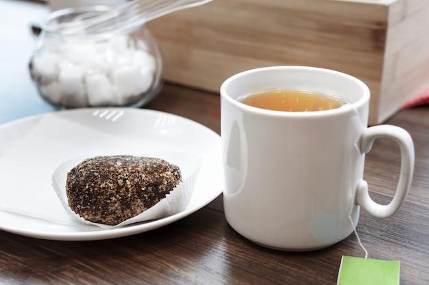 Eine tasse tee auf einem holztisch mit einem kuchen am fenster. das konzept eines morgenfrühstücks