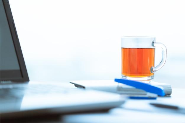 Eine tasse tee auf einem laptop.