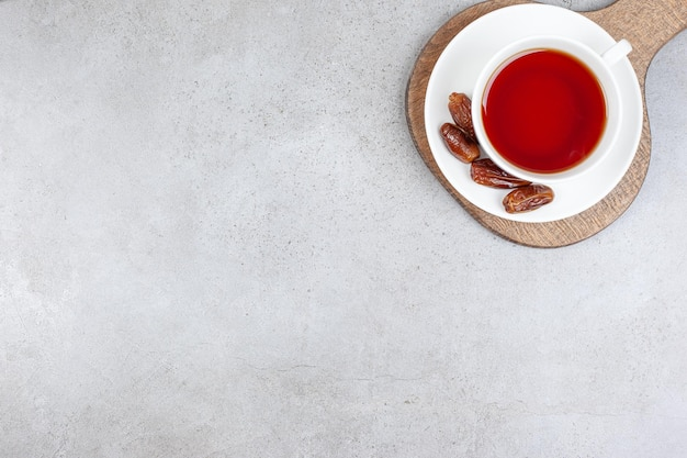 Eine tasse tee auf einer untertasse mit datteln auf einem holzbrett, auf marmorhintergrund. hochwertiges foto