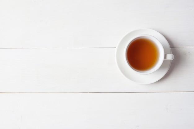 Eine tasse tee auf weißem hölzernem hintergrund.