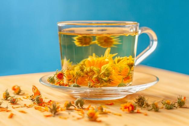 Eine tasse tee aus getrockneten ringelblumen, die vor- und nachteile, kochmethoden.