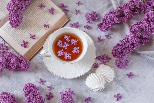 Eine tasse tee, baiser, zweige blühenden flieders und ein altes buch