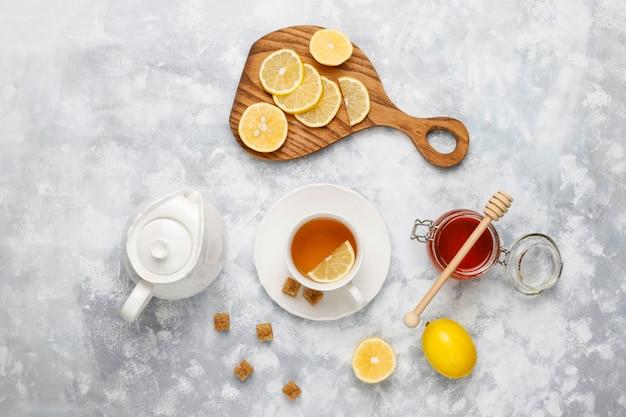 Eine tasse tee, brauner zucker, honig und zitrone auf beton. draufsicht, kopie, raum