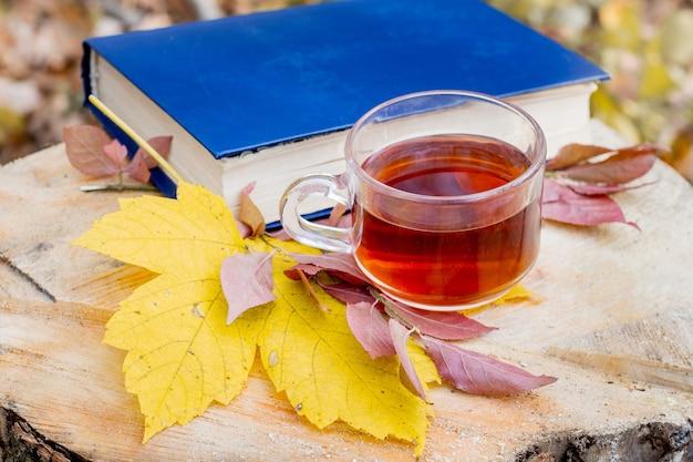 Eine tasse tee, ein buch und ein gelbes ahornblatt im wald auf einem baumstumpf. lesen sie bücher und frühstücken sie im wald