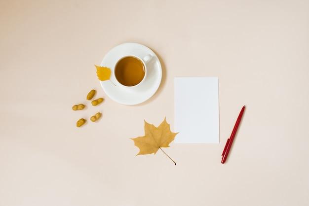 Eine tasse tee, ein sauberes weißes blatt papier, ein roter füllfederhalter, goldenes herbstlaub, erdnüsse in einer schale auf einem flachen hintergrundkopienraum des beigen hintergrunds. stillleben kaufmännische ausbildung.