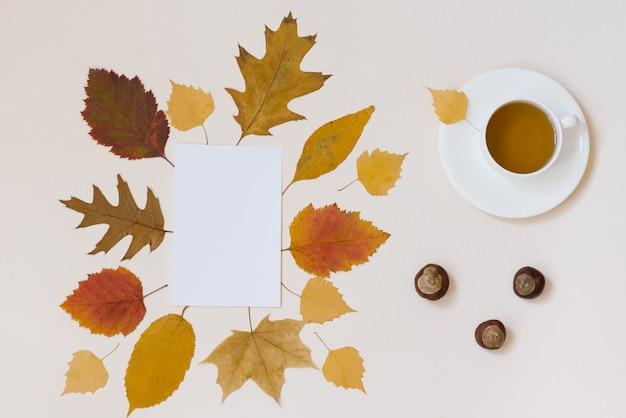 Eine tasse tee, ein sauberes weißes blatt papier, kastanien und herbstlaub