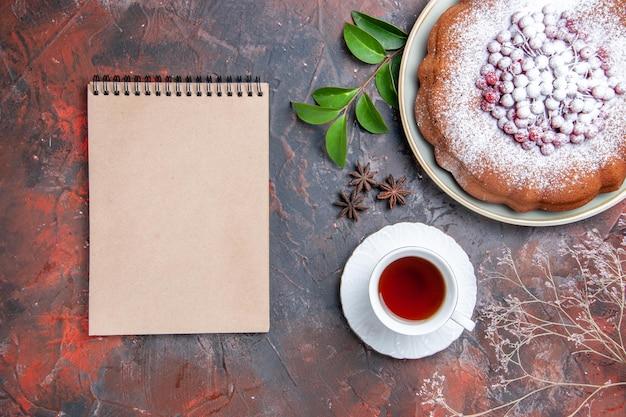 Eine tasse tee eine tasse schwarzen tee einen kuchen mit beeren notizbuch und blättern