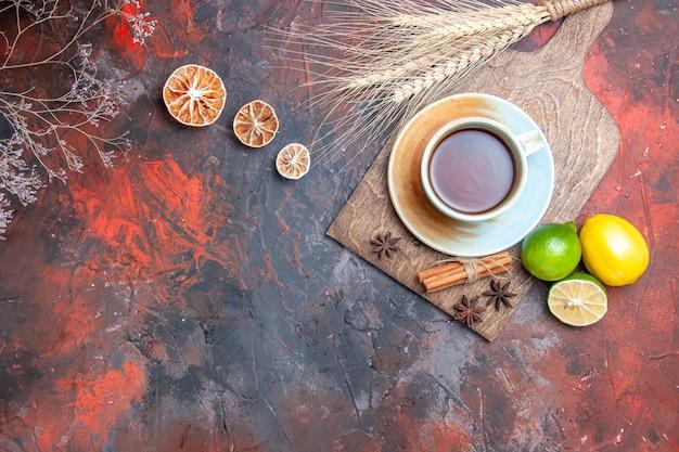 Eine tasse tee eine tasse tee zimt sternanis zitronen limetten auf dem schneidebrett
