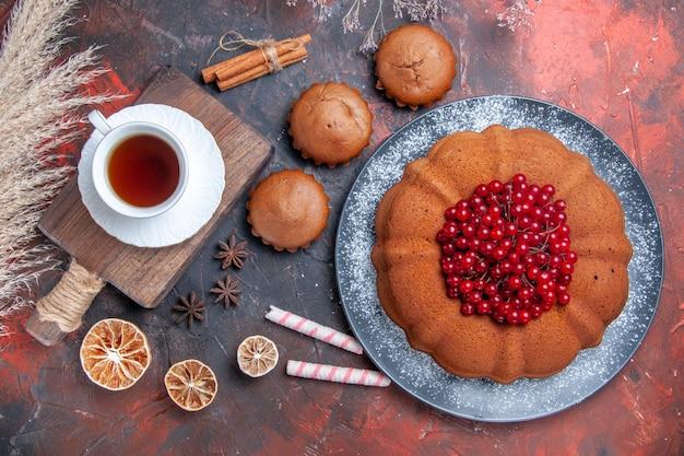 Eine tasse tee eine torte mit beeren zitronenbonbons eine tasse tee auf dem brett