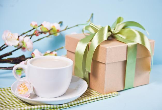 Eine tasse tee, geschenkbox und kirsche blühen mit blumen sakura an der blauen wand. frühlingskonzept.