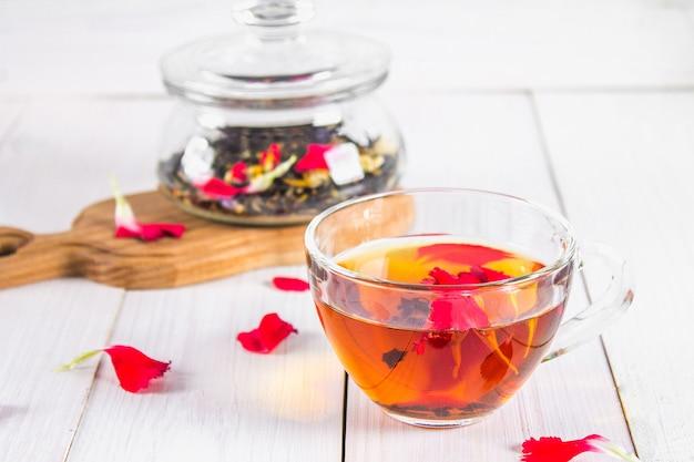 Eine tasse tee, im hintergrund einer bank mit einem schwarzen kräuterblumentee auf einem weißen holztisch.