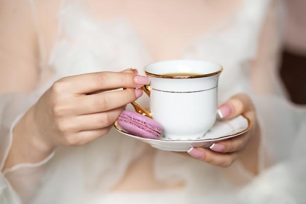 Eine tasse tee in den händen eines mädchens