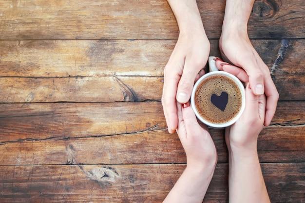 Eine tasse tee in den händen. selektiver fokus getränk.
