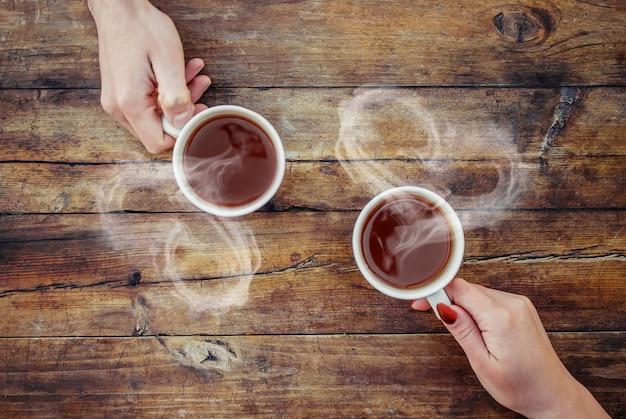 Eine tasse tee in den händen. selektiver fokus