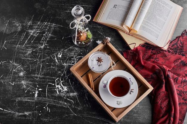 Eine tasse tee in einem holztablett, draufsicht.