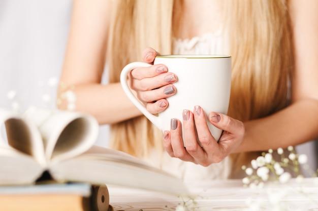 Eine tasse tee in frauenhand. konzept für den frühlingsmorgen. blumentee in einer weißen schale auf dem tisch mit büchern und blumen