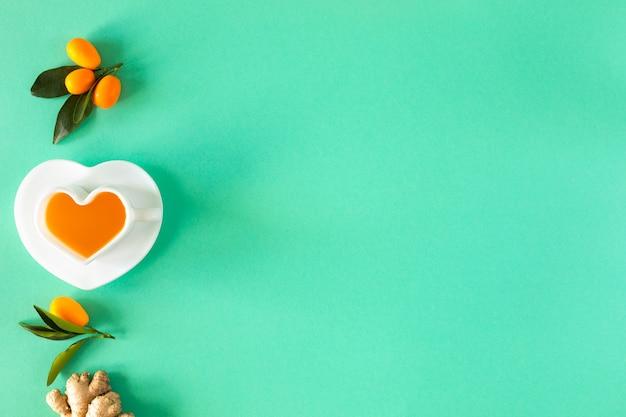Eine tasse tee, ingwer, curquat - vorbeugung von erkältungen. produkte zur stärkung der immunität auf grünem hintergrund. ansicht von oben. platz kopieren.