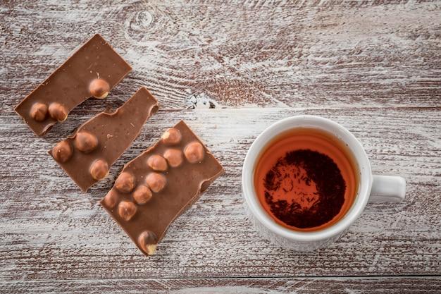 Eine tasse tee ist schwarze schokolade auf dem holz