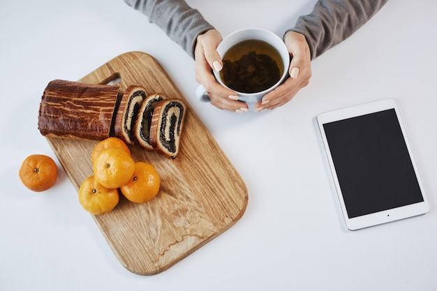Eine tasse tee lässt den morgen heller aussehen. moderne frau, die topf hält, mandarine und gerollten kuchen während des frühstücks oder mittagessens isst und darauf wartet, dass ihr chef ihre informationen über digitales tablet sendet