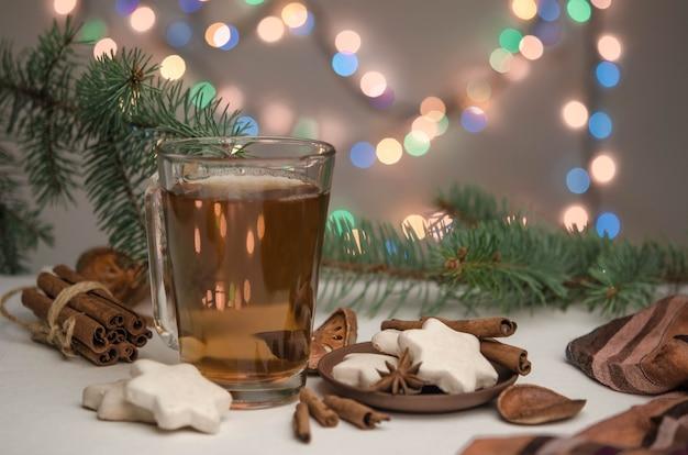 Eine tasse tee, lebkuchen und zimt auf bokeh-hintergrund